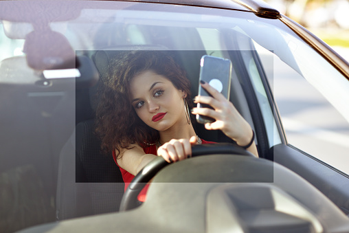 A female driver taking a selfie with a phone