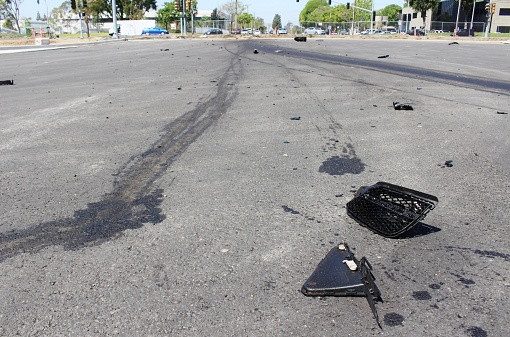 Car accident debris in the road from a hit and run crash