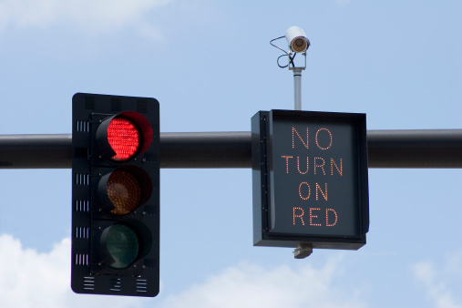 """Red traffic light with """"No Turn On Red"""" sign and intersection camera."""